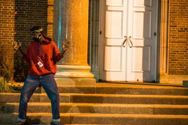 young black man in red sweatshirt and mask dances on the steps of a brick building.
