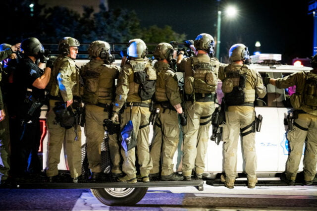 police officers and national guard in riot gear ride on the running boards of a denver police vehicle