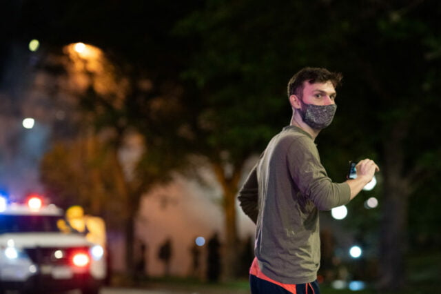 pedestrian in a face mask walking in front of a parked police car with lights on. Background is lit by street light and smoke and protesters can be seen