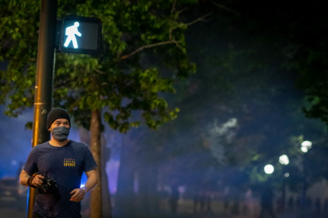 """Night time photographer with hat and mask walking away from park/protest positioned under a """"walk"""" street sign with smoke and pedestrians in the background"""