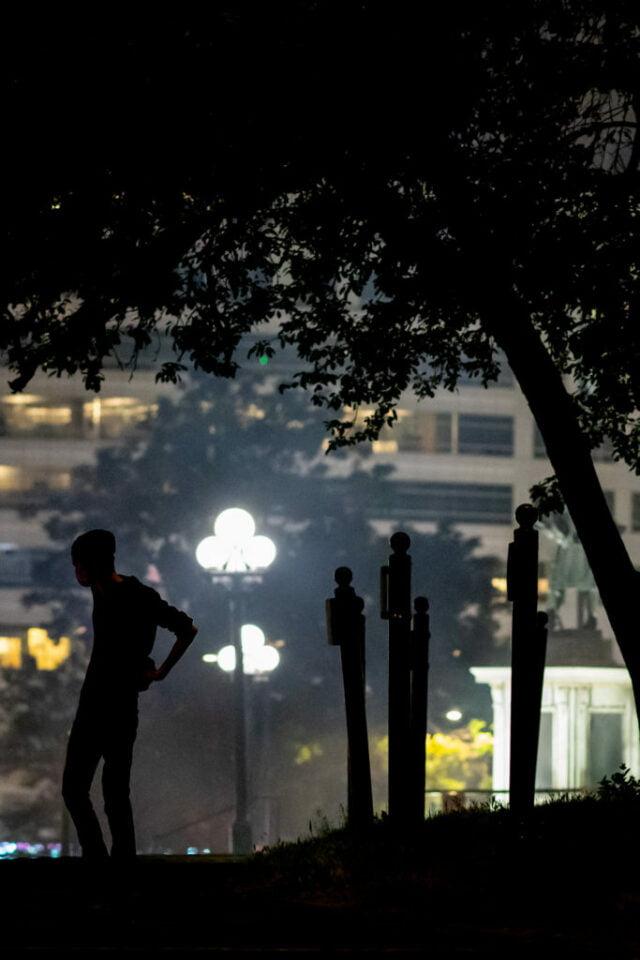 Single figure in silhouette in park.