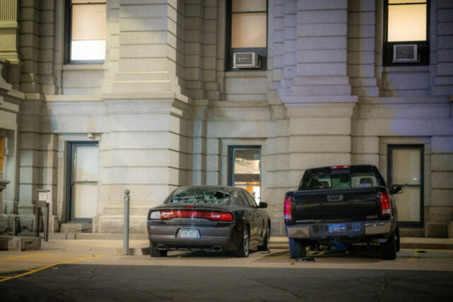 Two vandalized civilian cars parked outside of capitol building.