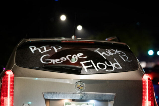 """Night time back window of tan SUV with """"RIP George Floyd"""" and """"Fuck 12"""" written in white letters on back window"""