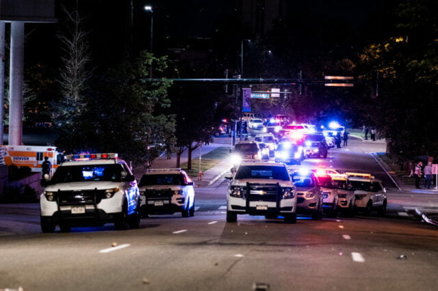 Seven police vehicles with their lights off approaching.