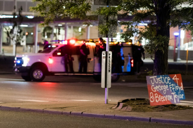 """Corner of Colfax and Lincoln, police officers ride on the running boards of the police vehicle. Protest sign in foreground reads """"Justice 4 George Floyd & Breonna Taylor"""""""