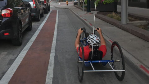Recumbent cycylist approaches an intersection in the bike lane along side traffic