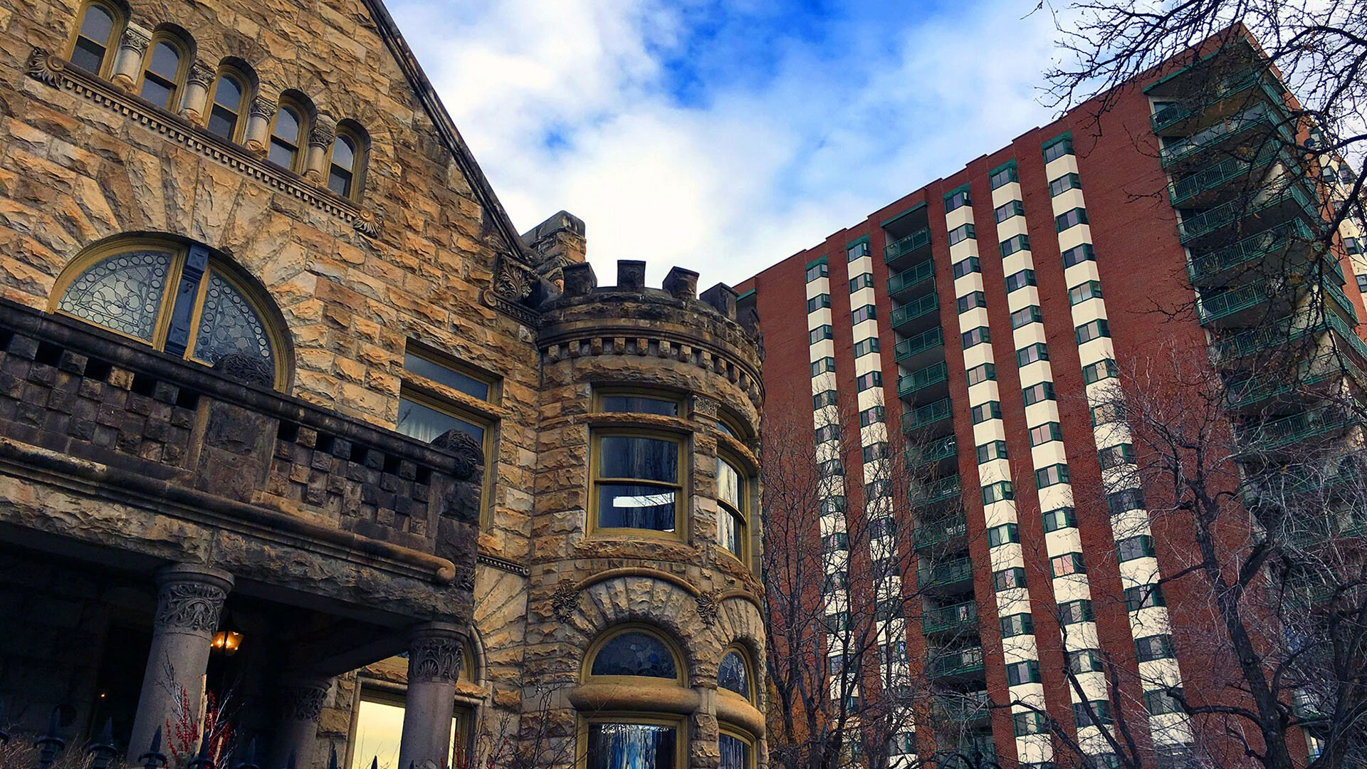 Historic brick building next to high-rise residential building. Sky is blue and partly cloudy. Trees in foreground are bare indicating winter