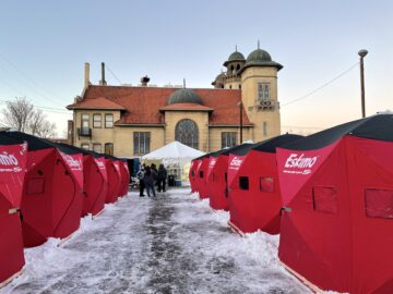Red Arctic-grade tents line a snowy path leading toward Denver Community Church