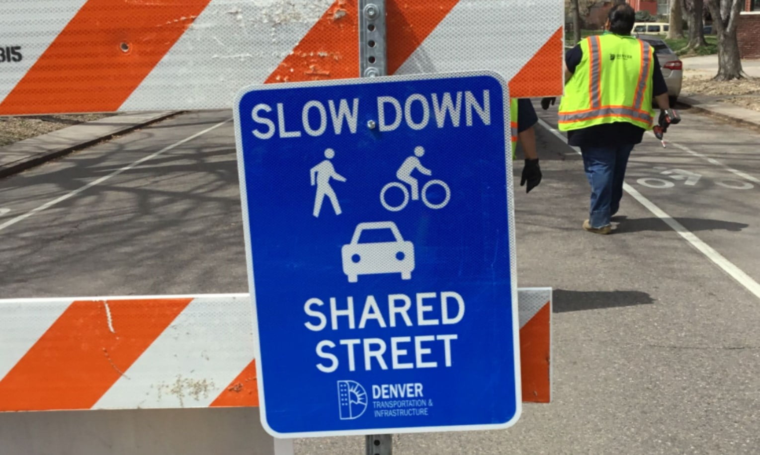 Photo of a traffic control sign stating that this street should be shared with bikes, people, and cars
