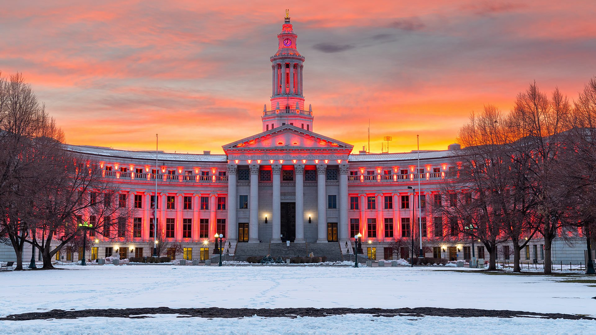 City and County of Denver building lit up red with sunset in background