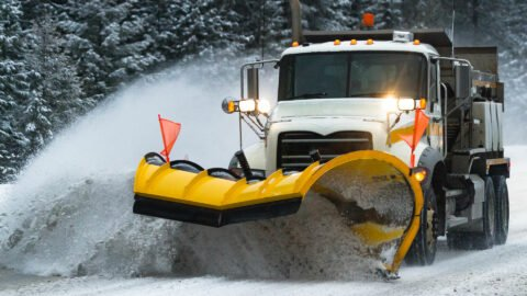 Denver snow plow pushes snow built up on the road to the shoulder