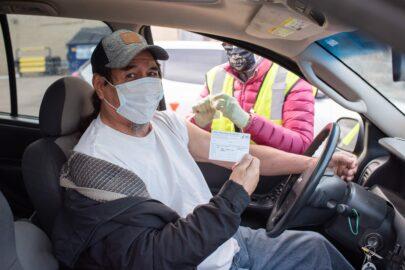 Man receiving a COVID-19 vaccine at a mobile drive-thru clinic.